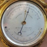 Miniature wall barometer with thermometer.