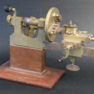 19th century brass and steel watchmaker lathe on wooden basement.