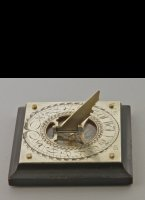 Ebonised and silvered brass sundial with colored paper rose and steel needle.